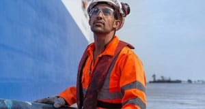 Traba Logistics sailor working on the paintjob on the side of the vessel.